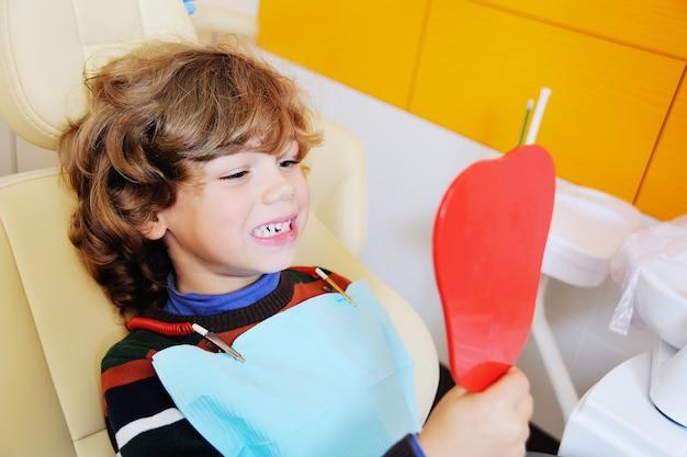 Ein kleiner junge mit lockigem haar in einem zahnarztstuhl öffnete den mund, um zu zeigen, wo er einen der zähne seines babys verloren hatte