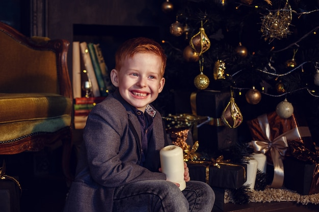 Ein kleiner junge mit roten haaren und sommersprossen auf einem dunklen hintergrund. gold und schwarz. weihnachtsbaum- und neujahrsdekorationen