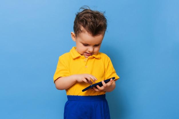Ein kleiner junge schaut auf den bildschirm eines mobiltelefons. studiofoto auf blauem hintergrund.