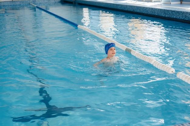 Ein kleiner junge schwimmt und lächelt im pool. gesunder lebensstil.