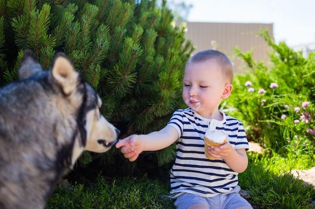 Ein kleiner junge sitzt auf dem hof und isst mit dem hund eis
