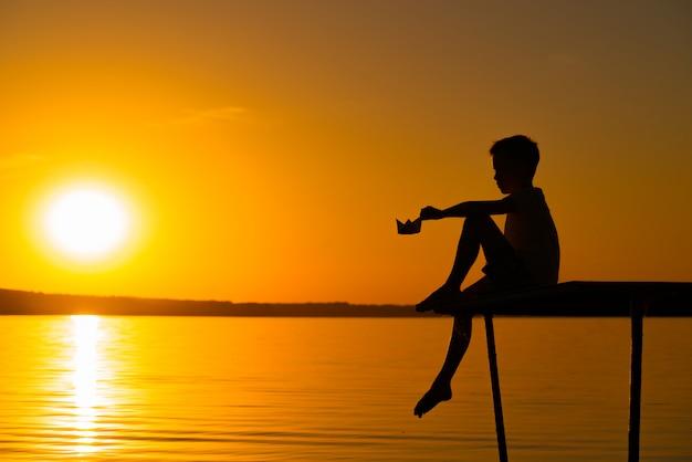Ein kleiner junge sitzt auf dem mauerwerk mit einem papierboot in der hand bei sonnenuntergang nahe dem fluss.