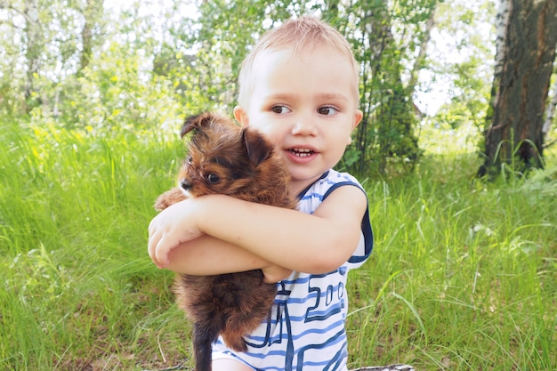 Ein kleiner junge sitzt im sommer im wald auf einem baumstumpf und umarmt einen kleinen braunen welpen.