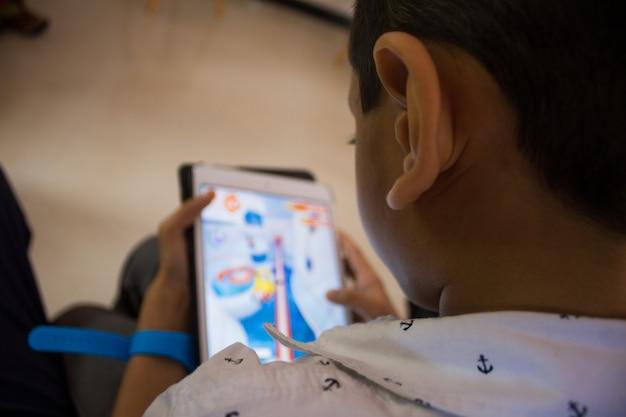 Ein kleiner junge spielt ein spiel auf seinem tablet
