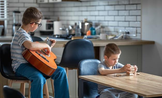 Ein kleiner junge spielt gitarre und sein bruder baut zu hause am tisch einen turm mit holzwürfeln.