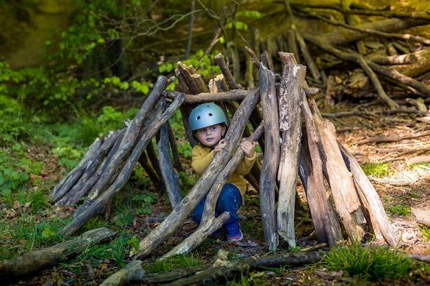 Ein kleiner junge spielt im sommer oder frühling im wald.