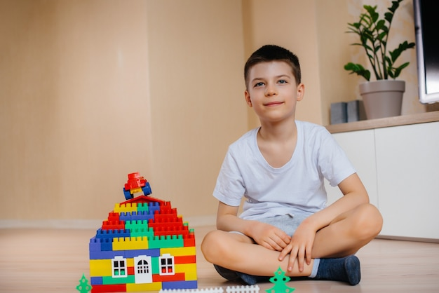 Ein kleiner junge spielt mit einem baukasten und baut ein großes haus für die ganze familie. bau eines einfamilienhauses.