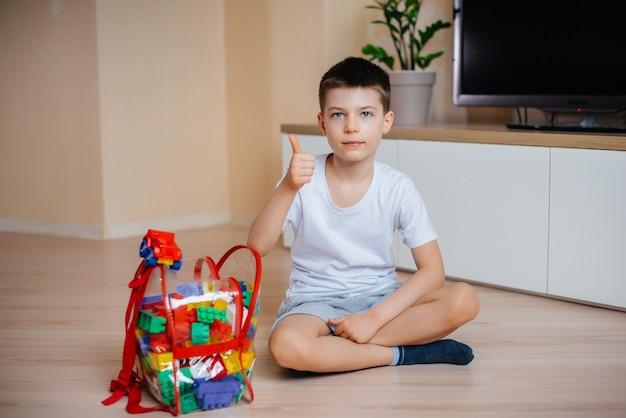 Ein kleiner junge spielt mit einem bausatz und baut ein großes haus für die ganze familie. bau eines einfamilienhauses.