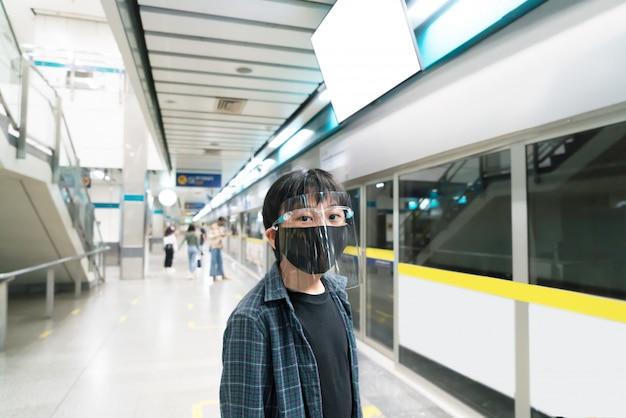 Ein kleiner junge trägt einen gesichtsschutz und gesundheitsmasken für reisen mit öffentlichen verkehrsmitteln.