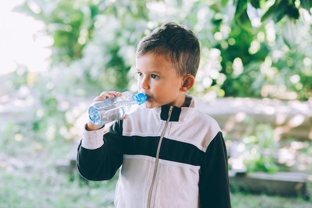 Ein kleiner junge trinkt draußen wasser aus einer blauen flasche