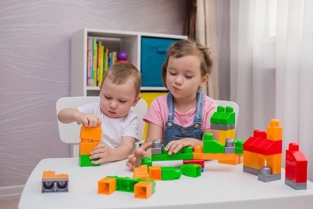 Ein kleiner junge und ein mädchen spielen an einem tisch in einem raum ein konstrukteurspiel
