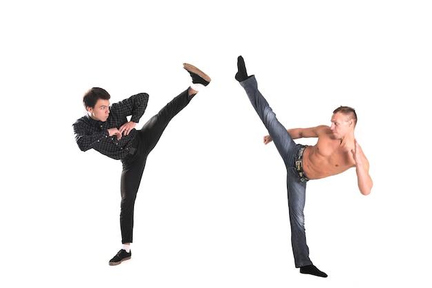 Ein kleiner junge und ein mann porträtierten karate isoliert auf weißem hintergrund