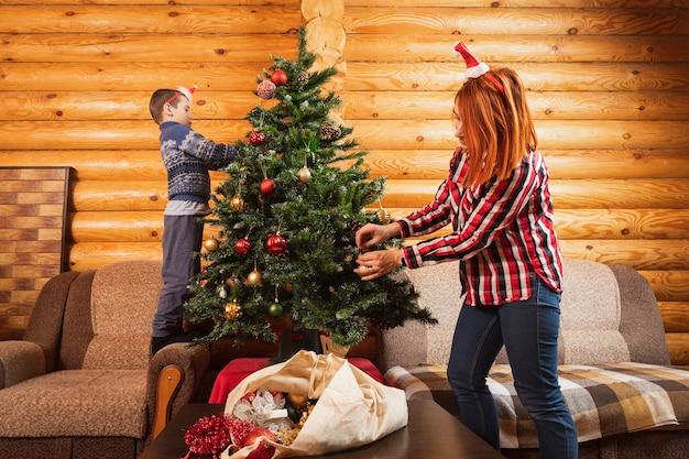 Ein kleiner junge und eine kleine mutter schmücken einen künstlichen weihnachtsbaum mit glaskugeln in einem landhaus