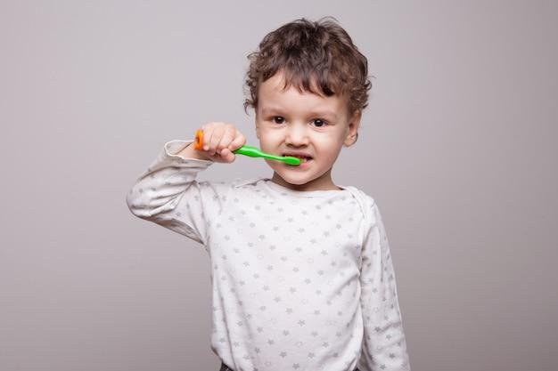 Ein kleiner junge von drei jahren putzt sich die zähne