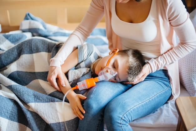 Ein kleiner junge wird von seiner mutter während einer lungenerkrankung inhaliert. covid19, coronavirus, pandemie.