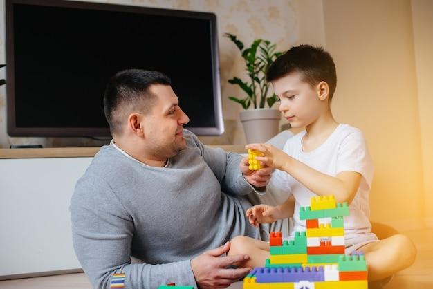 Ein kleiner junge wird zusammen mit seinem vater von einem bauunternehmer gespielt und baut ein haus. bau eines einfamilienhauses. Premium Fotos