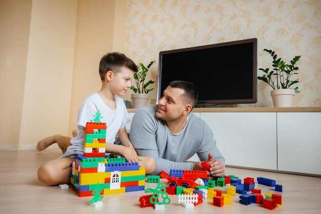 Ein kleiner junge wird zusammen mit seinem vater von einem bauunternehmer gespielt und baut ein haus. bau eines einfamilienhauses.