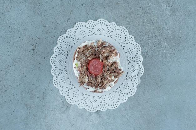 Ein kleiner kuchen auf einem deckchen auf marmorhintergrund. hochwertiges foto