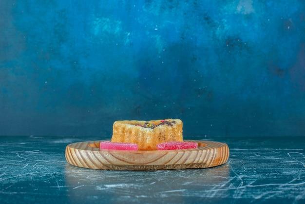 Ein kleiner kuchen und marmeladen auf einer hölzernen platte auf blauem hintergrund. hochwertiges foto