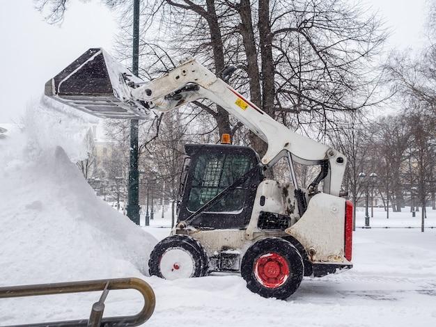 Ein kleiner lader mit einem eimer gießt bei starkem schneefall schnee in einen großen haufen in einem stadtpark. schneeflocken fliegen durch die luft. wintertag.