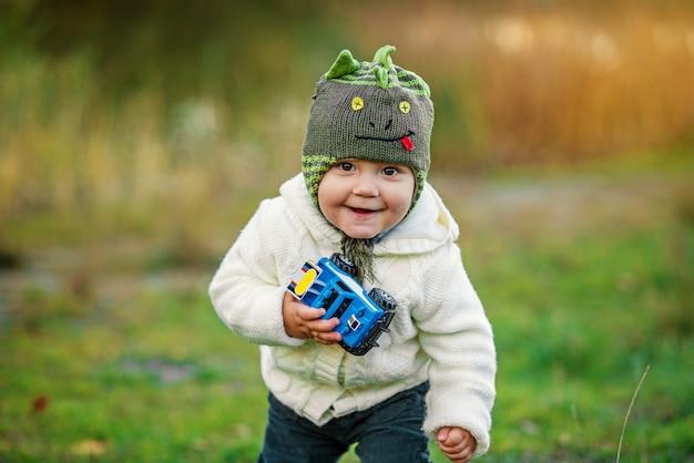 Ein kleiner lächelnder junge in der warmen kleidung, die mit blauem spielzeugauto auf dem grünen rasen auf dem sonnenuntergang spielt.