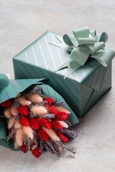 Ein kleiner lavendelstrauß mit lagurus und ein geschenk in türkiser verpackung