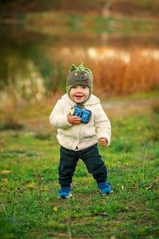 Ein kleiner lustiger junge mit zwei zähnen in der warmen kleidung, die in der nähe des sees auf dem sonnenuntergang spielt.