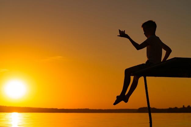 Ein kleiner mann sitzt auf einer brücke und hält origami von papierschiff in der hand am abend bei sonnenuntergang. ein junge spielt mit seinem spielzeug am fluss