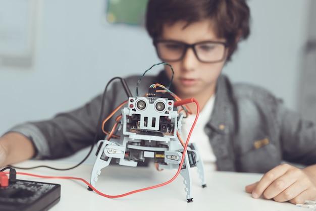 Ein kleiner nerd schaut sich seine kreation genau an