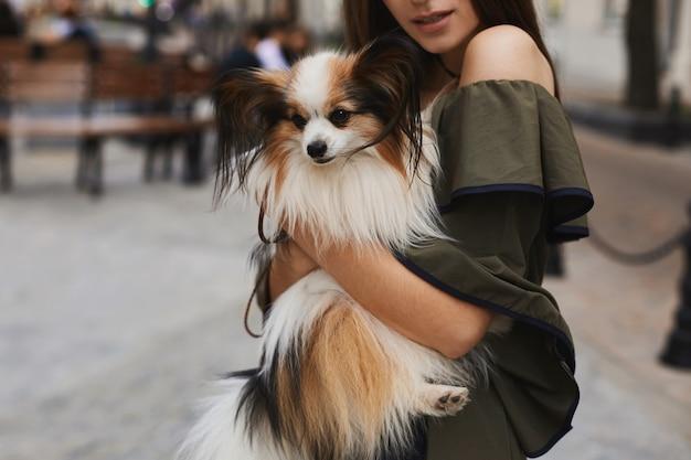 Ein kleiner niedlicher papillon-hund auf den händen eines schönen und fröhlichen brünetten modellmädchens im kurzen kleid, das draußen im alten stadtzentrum aufwirft