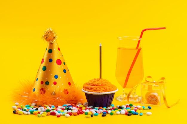 Ein kleiner orangefarbener kuchen der vorderansicht mit kerze zusammen mit süßigkeiten trinken auf dem gelben schreibtischfarbbonbonkuchen