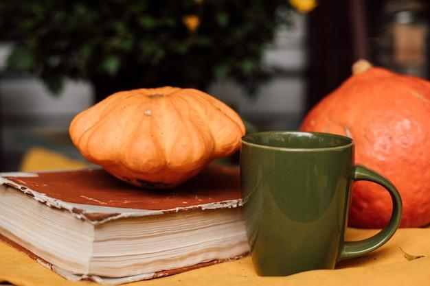 Ein kleiner orangefarbener kürbis liegt neben einem buch und einer grünen tasse
