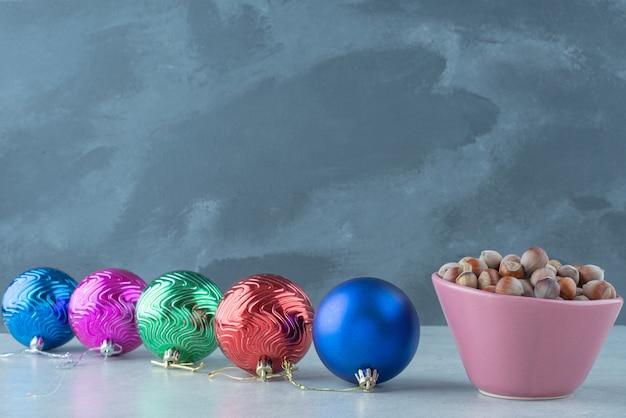 Ein kleiner rosa teller voller nüsse mit weihnachtskugeln auf marmorhintergrund. hochwertiges foto