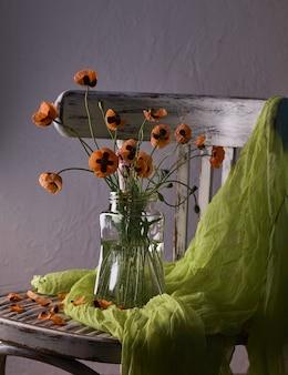 Ein kleiner roter mohnblumenstrauß arrangiert im klassischen stil stilleben von mohnblumen in einer gläservase auf vintage-stuhl