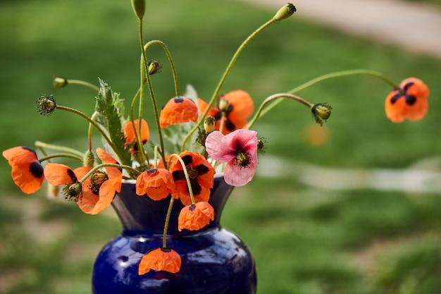 Ein kleiner roter mohnblumenstrauß im klassischen stil arrangiert