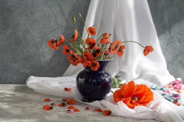 Ein kleiner roter mohnblumenstrauß in blauer keramikvase
