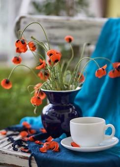 Ein kleiner roter mohnblumenstrauß in blauer vase auf vintage-stuhl. mohnblumen und tasse kaffee.