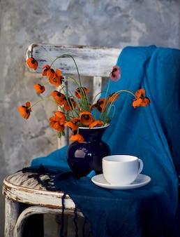 Ein kleiner roter mohnblumenstrauß in der blauen vase auf vintage-stuhl. mohn und eine tasse kaffee.