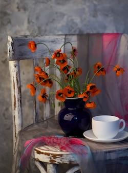 Ein kleiner roter mohnblumenstrauß in der blauen vase auf vintagen stuhl. mohn und eine tasse kaffee.