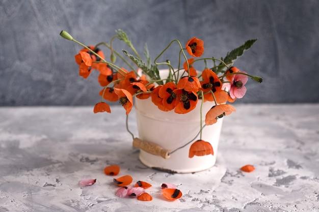 Ein kleiner roter mohnblumenstrauß in weißer vase. stillleben mit wildem mohn.