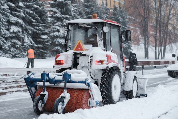 Ein kleiner roter traktor mit einer bürste fegt bei starkem schneefall schnee vom bürgersteig in der nähe der kremlmauern. schneeflocken fliegen durch die luft.