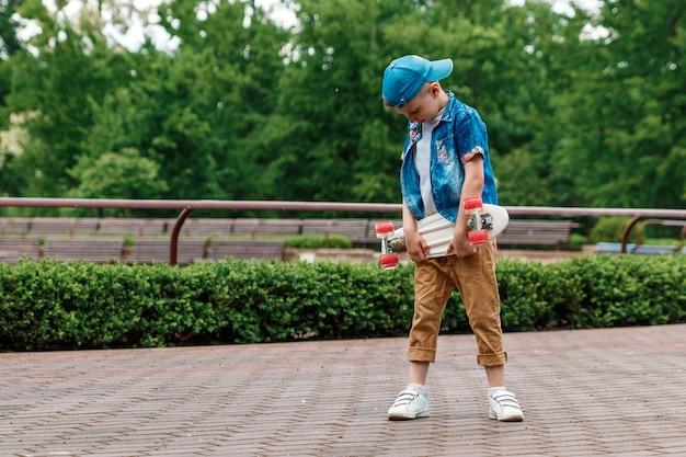 Ein kleiner stadtjunge andskateboard. ein junger mann steht im park und hält ein skateboard