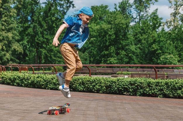 Ein kleiner stadtjunge und ein skateboard. ein junger mann fährt in einem park auf einem skateboard