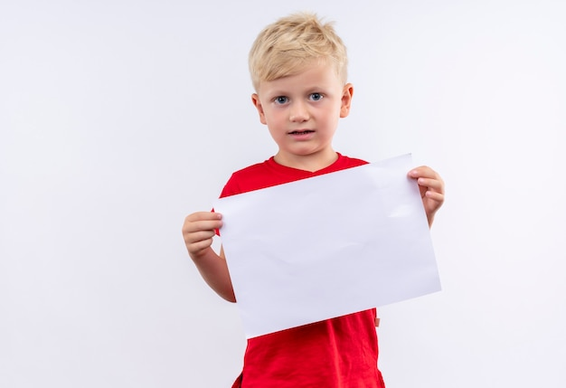 Ein kleiner süßer blonder junge im roten t-shirt, der leeres blatt papier hält, während auf einer weißen wand schaut