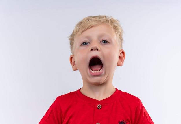Ein kleiner süßer blonder junge im roten t-shirt öffnet seinen mund und schreit, während er auf eine weiße wand schaut