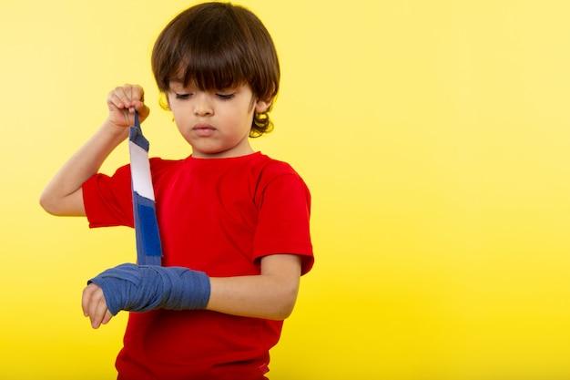 Ein kleiner süßer junge der vorderansicht, der seine hand mit blauem taschentuch im roten t-shirt an der gelben wand bindet