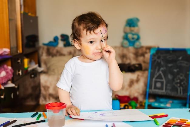 Ein kleiner süßer junge zeichnet mit pinseln und farbigen farben auf ein blatt papier