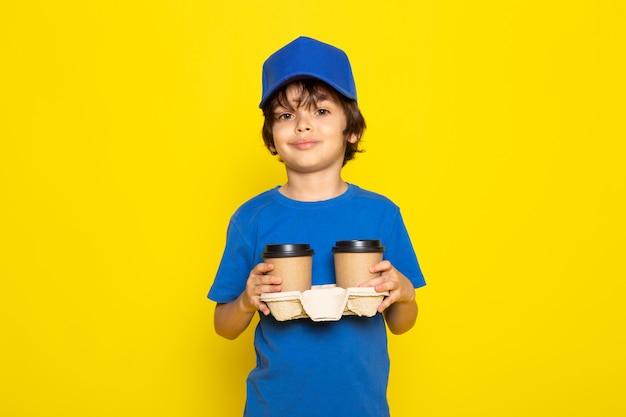 Ein kleiner süßer kurier der vorderansicht in der blauen kappe des blauen t-shirts, die kaffeetassen hält