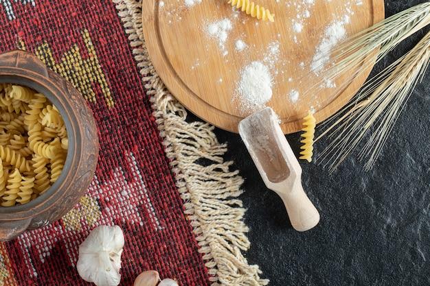 Ein kleiner topf mit unvorbereiteten spiralmakkaroni mit knoblauch und mehl