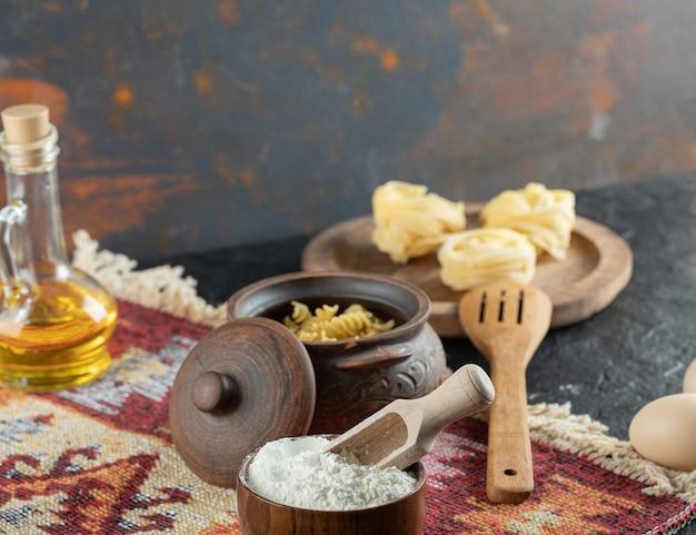 Ein kleiner topf mit unvorbereiteten spiralmakkaroni mit löffel und mehl